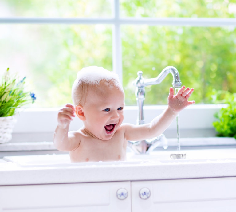 happy baby splashing in bath