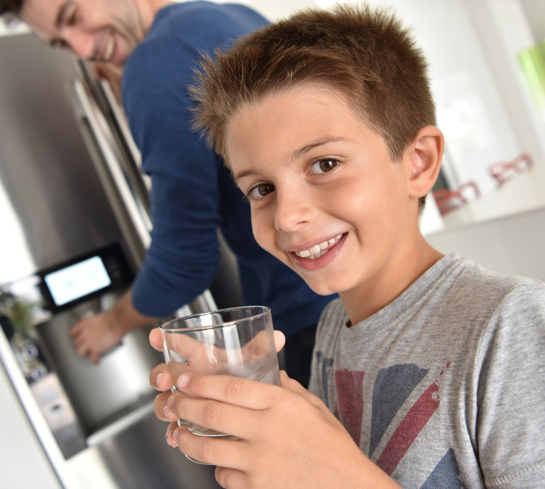 boy drinking water from fridge